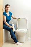 Woman cleaning toilet bowl with sponge Royalty Free Stock Photos