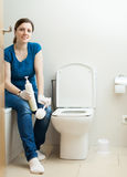 Woman cleaning toilet with brush and cleaner at  home Stock Image