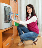 Woman cleaning TV with cleanser Stock Images
