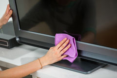 Woman cleaning TV with cleanser at home Royalty Free Stock Photography