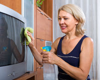 Woman  cleaning TV with cleanser Royalty Free Stock Photos