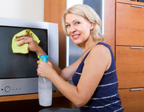 Woman  cleaning TV with cleanser. Mature woman  cleaning  screen of TV with cleanser at home Royalty Free Stock Photo