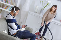Woman cleaning up while husband relaxing on sofa Stock Photos