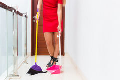 Woman cleaning up sweep floor with broom and shovel. Woman or housewife cleaning up sweep floor with hand broom and shovel Royalty Free Stock Photos