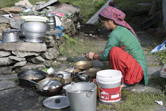 A woman cleaning utensils outdoor. A woman cleaning utensils outdoor in Shimla, Himachal Pradesh, India Royalty Free Stock Photography