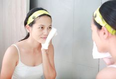 Woman cleaning washing her face with towel reflect with bathroom mirror.  Royalty Free Stock Photography