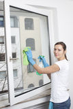 Woman cleaning a window Royalty Free Stock Image
