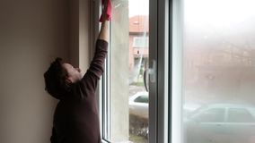 Woman cleaning window. With rag and cleanser spray at home stock footage