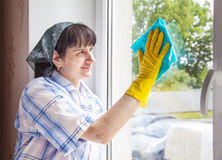 Woman cleaning a window with a rag Royalty Free Stock Image