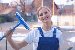 Woman cleaning window with scraper, view glass Royalty Free Stock Images