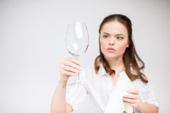 Woman cleaning wine glass. Young concentrated woman holding rag and looking at clean wine glass stock images