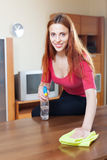 Woman cleaning wooden table with rag and cleanser Stock Image