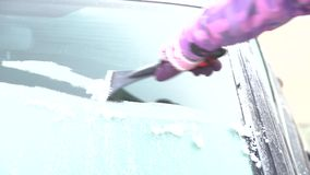 Woman cleans the car window from the snow and ice with a scraper stock video footage