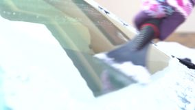 Woman cleans the car window from the snow and ice with a scraper stock footage