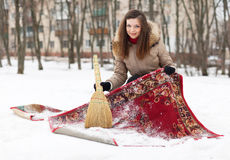 Woman cleans carpet with snow Royalty Free Stock Image