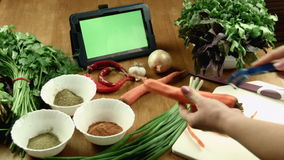 The woman cleans carrot and watches the recipe in the tablet