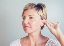 Woman cleans ears with cotton sticks on white stock images
