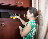 Woman cleans a furniture indoor Royalty Free Stock Image