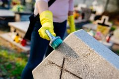 Woman cleans a grave with brush. November 1 All Saints' Day Royalty Free Stock Photography