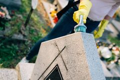 A woman cleans the grave. Royalty Free Stock Photo