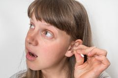 Woman cleans her ears with cotton swab. Hygiene concept royalty free stock images