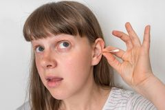 Woman cleans her ears with cotton swab royalty free stock images