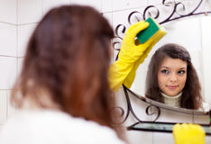 Woman cleans mirro. R in bathroom at home royalty free stock images
