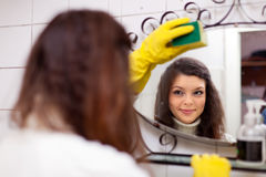 Woman cleans  mirror in bathroom Stock Images