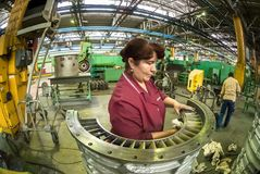 Woman cleans part for aviation engine Stock Photography
