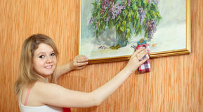 Woman cleans picture at home Stock Photography