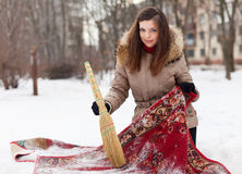 Woman cleans red carpet with snow. Smiling woman cleans red carpet with snow in winter day Royalty Free Stock Image