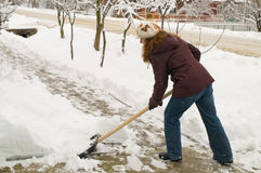 The woman cleans snow. Stock Photo