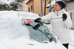 Woman cleans snow from the car Royalty Free Stock Image