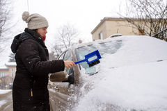 Woman cleans snow car Royalty Free Stock Photo
