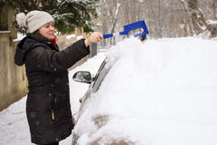 Woman cleans snow car Royalty Free Stock Photography