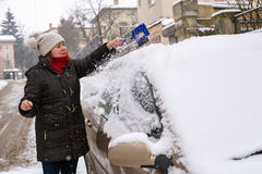 Woman cleans snow car Royalty Free Stock Photos