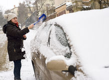 Woman cleans snow car Stock Photo