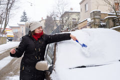 Woman cleans snow car Stock Images