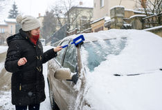 Woman cleans snow car Royalty Free Stock Image