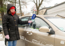 Woman cleans snow car windshield Royalty Free Stock Image