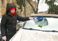 Woman cleans snow car windshield Royalty Free Stock Images