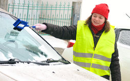 Woman cleans snow car windshield Stock Photography
