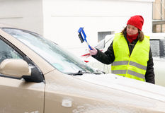 Woman cleans snow car windshield Royalty Free Stock Photo