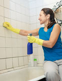 Woman cleans tile with sponge in bathroom Stock Image