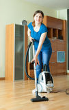 Woman cleans with vacuum cleaner Royalty Free Stock Photos