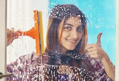 Woman cleans the window with a brush Royalty Free Stock Image