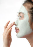 Woman with cleansing mud mask. Orient woman with cleansing mud mask on the face Royalty Free Stock Photo
