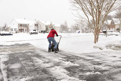 Woman clearing driveway with a snowblower Stock Photography