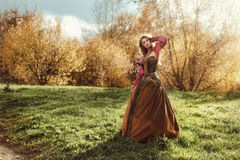 Woman in a clearing in the sun. Beautiful woman in historic dress enjoying the sunlight on nature Stock Images