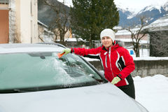 The woman clears car wind screen Stock Images